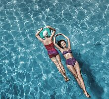 1948 Fashion models posing in bathing suits floating in a swimming pool by Marie-Lou Chatel