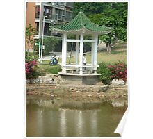 shimmering reflections while man fishes from colourful pagoda Poster