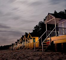 torch lit beach huts by Julian Marshall