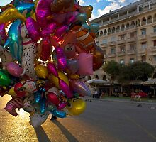 Lots of colorful balloons in a city square plaza by Byzas
