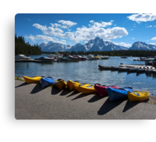 Red, Yellow and Blue Canoes on Shore Canvas Print
