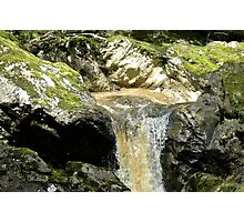 Peaty water over mossy rocks Photographic Print
