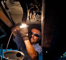 Mechanic soldering a muffler by Eyal Nahmias