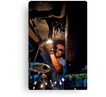 Mechanic soldering a muffler Canvas Print