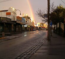 Wet rainy street in the sunlight with a rainbow by StefanoB