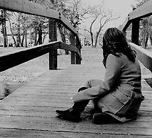 Girl sitting on bridge by Kelly S