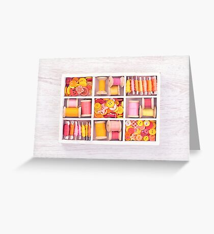 Collection of yellow, red, pink spools  threads  arranged in a white wooden box Greeting Card