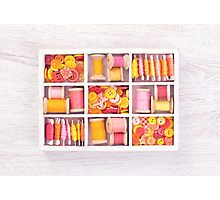 Collection of yellow, red, pink spools  threads  arranged in a white wooden box Photographic Print