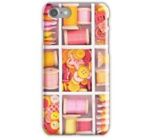Collection of yellow, red, pink spools  threads on in a white wooden box iPhone Case/Skin
