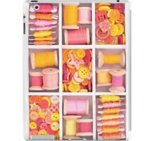 Collection of yellow, red, pink spools  threads on in a white wooden box iPad Case/Skin