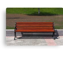 new wooden bench in a city park Canvas Print