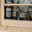Bottles in weathered window by ashley hutchinson