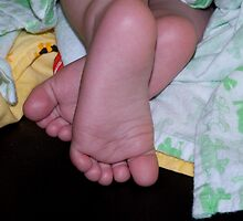 Feet poking out from green & yellow blankee by Lanii  Douglas
