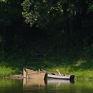 Stairs and two boats in the river by Antanas