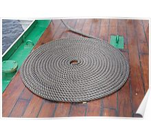 A grey rope in a circle on the varnished deck of Gloria. Poster