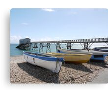 White, yellow and blue wooden boats on pebble beach Canvas Print