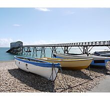 White, yellow and blue wooden boats on pebble beach Photographic Print