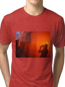 The shadow of a man on a red-orange wall, who photographs a road sign Tri-blend T-Shirt