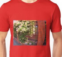 Facade of the building with a brick wall with flowers Unisex T-Shirt