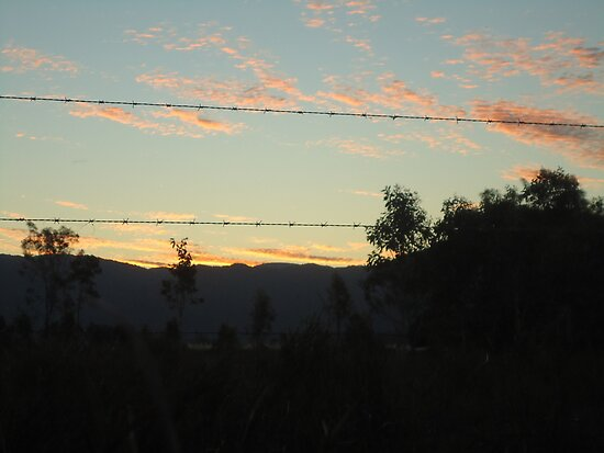 sunset through barb wire fence by myhobby