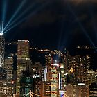 Laser show over city at night, Hong Kong, China. by Sami Sarkis