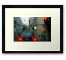 Traffic lights in rain, view through windscreen Framed Print