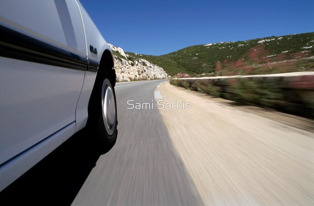 Speeding  car on road by Sami Sarkis