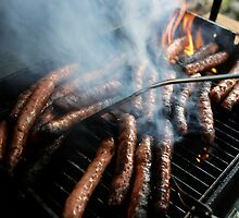Sausages cooking on barbecue by Sami Sarkis