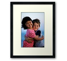 Girl and boy (7-9) embracing, outdoors, smiling, portrait Framed Print