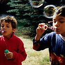 Girl and boy (7-9) blowing bubble-wands, outdoors by Sami Sarkis