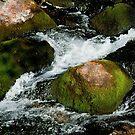 Water stream breaks on the rocks by Dfilyagin