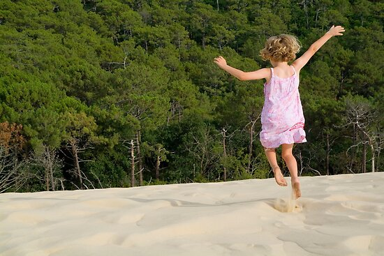 Little girl jumping in sand by Sami Sarkis