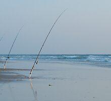 Three fishing rods on beach by Sami Sarkis
