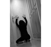 Woman kneeling in corridor with hands on closed door, asking for help Photographic Print