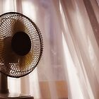 Electric fan beside apartment window with white curtains by Sami Sarkis
