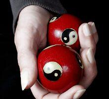 Woman holding Yin Yang balls in hand by Sami Sarkis