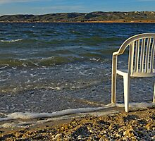 Plastic chair on water edge on beach by Sami Sarkis