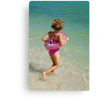 Girl running into water on beach Canvas Print