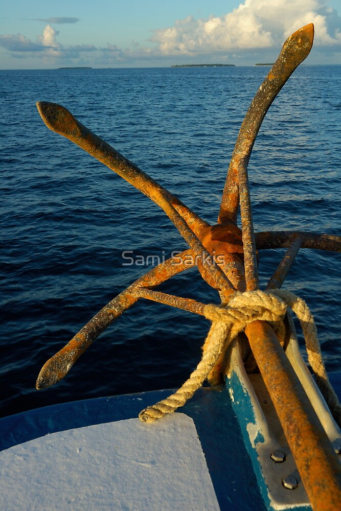 Rusty anchor on back of boat by Sami Sarkis