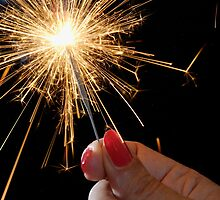 Woman holding sparkler by Sami Sarkis
