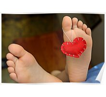 Valentine heart hanging on girl's (6-7) barefeet Poster