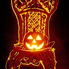 Carved smiling pumpkin on chair by Garry Gay