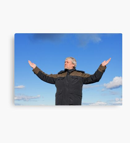Middle-aged man on blue sky of the background. Canvas Print