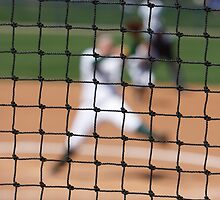 Softball Game - Blurred Pitcher Seen Through the Focused Backstop Net by Buckwhite
