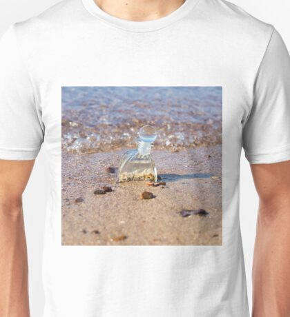 A bottle with seashells embedded in the sand on the beach  Unisex T-Shirt