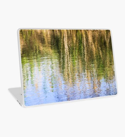 trees on the river bank reflect in the rippling water of the river  Laptop Skin