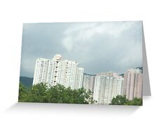 Apartment building towering over trees on mountain side Greeting Card