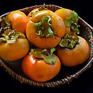 persimmons in a bowl by David Chesluk