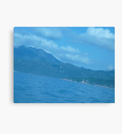 Puffy clouds floating over Island Canvas Print