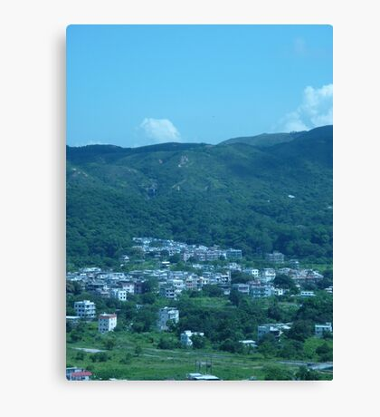 Mountains surrounding a little village Canvas Print